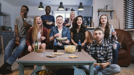 Friends watch sports on TV, cheer and celebrate. Happy diverse supporters fans sit on couch with popcorn and drinks. Stok Fotoğraf