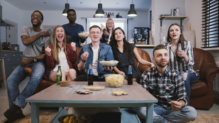Friends watch sports on TV, cheer and celebrate. Happy diverse supporters fans sit on couch with popcorn and drinks. 4K. Stok Fotoğraf