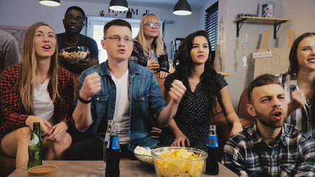 Multi ethnic supporters watching sports on TV. 4K slow motion. Sports fans cheer together for favourite team. Emotion. Banco de Imagens - 103162733