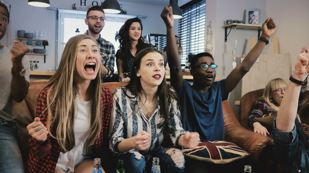 Multi ethnic supporters watch sports game on TV.  Diverse football fans celebrate goal moment. Emotion. Banco de Imagens