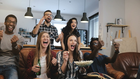 Cross-cultural group watch sports game on TV. Passionate supporters celebrate goal with drinks. Stock Photo