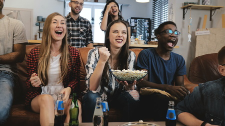 Mixed ethnicity group watching sports game on TV. Emotional fans on couch with drinks and snacks Stok Fotoğraf