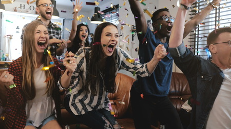 Emotion. Multi-ethnic fans celebrate winning. Passionate supporters shout watching game on TV. Stock Photo