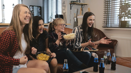 Female friends watch comedy film at home on TV. Happy girls laugh watching funny action movie together 4K slow motion. Stock Photo