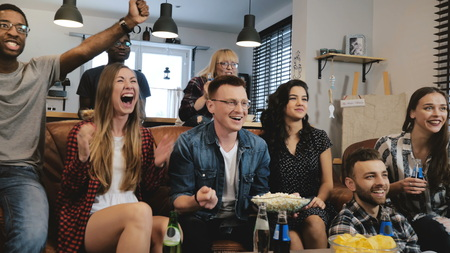 Mixed ethnicity friends watching funny film on TV. Medium shot. Passionate and cheerful football fans. Stock Photo