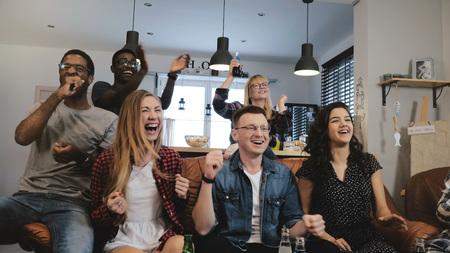 Diverse football fans get wild celebrating win 4K slow motion. Happy multi ethnic friends watching sports on TV. Emotion Banco de Imagens - 103162739