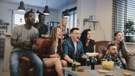 Multi-ethnic happy sports fans celebrate goal. 4K slow motion. African American friends support favourite team on TV.