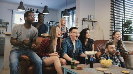 Multi-ethnic happy sports fans celebrate goal. 4K slow motion. African American friends support favourite team on TV. Banco de Imagens - 103162740