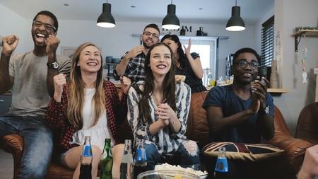 Multi-ethnic fans go crazy celebrating goal on TV.