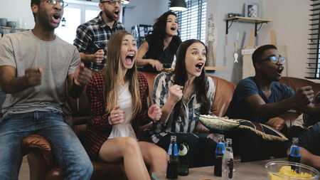 African American sports fans celebrate win at home. Passionate supporters shout watching game on TV. 4K slow motion. Stock Photo