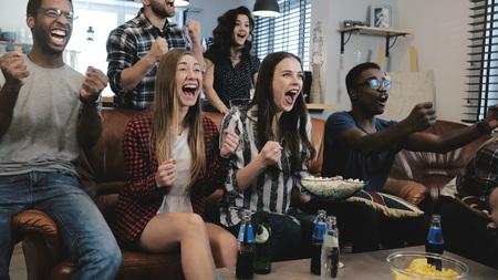ventiladores afroamericanos de los aficionados americanos celebran trucos en los juegos olímpicos de lectura de los estudiantes que miran la televisión en la televisión