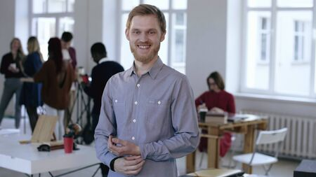 Portrait of young confident successful European male executive manager looking at camera smiling in modern light office.