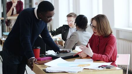 Happy young black male manager talking to middle aged European boss woman, multiethnic people at modern healthy office. Casual African man working together with beautiful female leader in red dress.