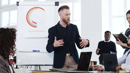 Happy successful Caucasian middle aged boss businessman explaining sales diagram to workers at modern office conference. Stock Photo
