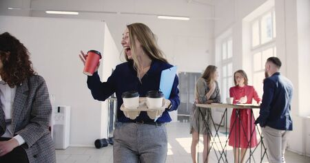 Beautiful successful blonde woman boss with coffee cups entering multiethnic office, talking to happy employees smiling.