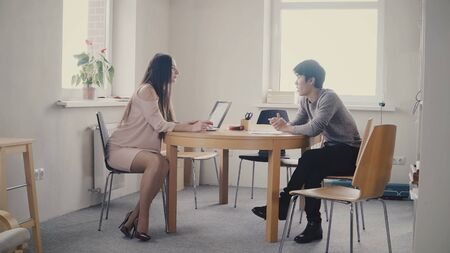 Young Asian man talking to confident businesswoman by the table. Multiethnic people talk in trendy modern office 4K.