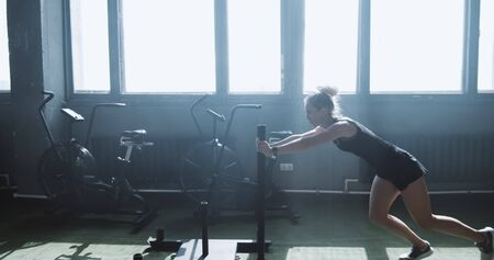 Dolly shot young athletic blonde woman working out with functional training sled in big atmospheric gym slow motion.
