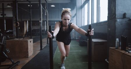 Motivation concept, young athletic blonde woman pushing heavy training sled towards camera training in gym slow motion.