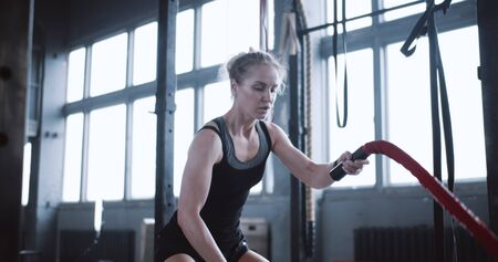 Young beautiful determined athletic blonde woman exercising with battle ropes, functional training workout in large gym.
