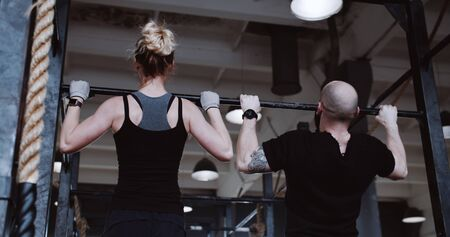 Back view young athletic Caucasian man and woman working out doing pull-ups slow motion. Healthy lifestyle concept.