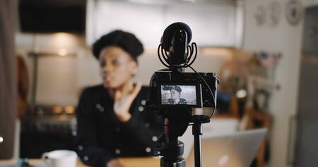 Close-up professional camera is filming young beautiful African blogger woman creating new vlog video slow motion.
