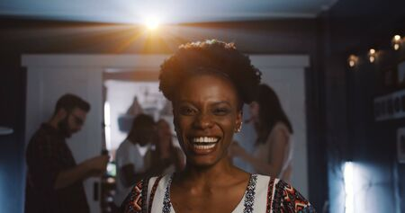 Portrait of happy beautiful young African woman smiling at camera at fun birthday celebration dance party slow motion.