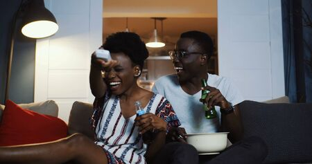 Happy positive young African man and woman smile and talk watching TV, using remote at home with snacks slow motion. Banco de Imagens