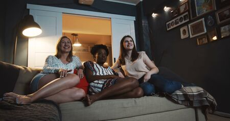 Happy beautiful multiethnic women watch comedy movie, laugh together at home with snacks using projector slow motion. Imagens