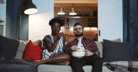 Happy young Caucasian man and African woman sit at home watching dramatic movie together, eating popcorn slow motion.