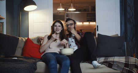 Happy young casual European romantic couple watching TV series at home, smiling and talking, eating popcorn slow motion