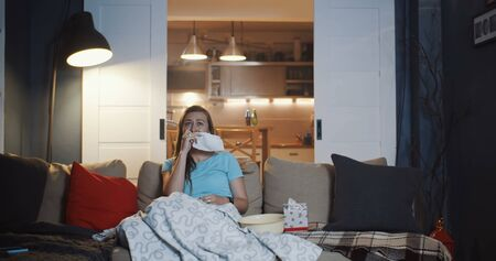 Sad young attractive European woman crying, wiping tears with tissue watching drama movie on TV at home slow motion.