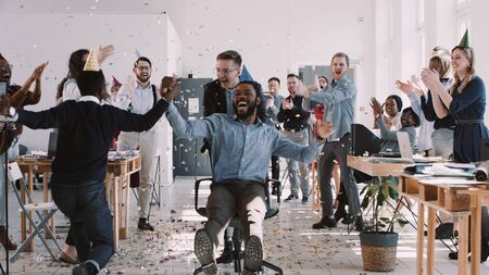 Happy young black businessman celebrating birthday at office workplace party with confetti slow motion.