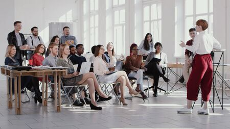 Group of happy multiethnic business people listen to female coach speaking at modern office seminar slow motion