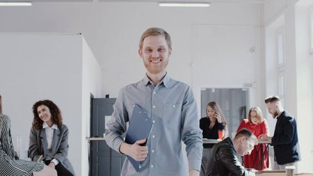 Happy successful young Caucasian businessman walking along modern light office smiling at camera slow motion Foto de archivo