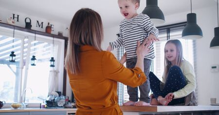 Happy young Caucasian mother and father playing with cute little sons in house kitchen, family fun concept slow motion.
