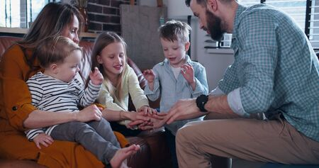 Happy young Caucasian family with three kids join hands and cheer up together, togetherness time at home slow motion. Imagens