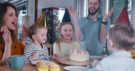 Happy young Caucasian teenage girl child celebrating birthday with family, blowing on cake candles at home slow motion. Imagens