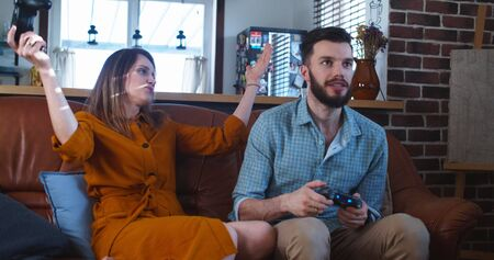 Young happy European couple of friends have fun playing a difficult videogame at home enjoying free time slow motion.