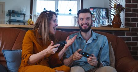 Happy young Caucasian man and woman friends compete against each other playing console video game at home slow motion.