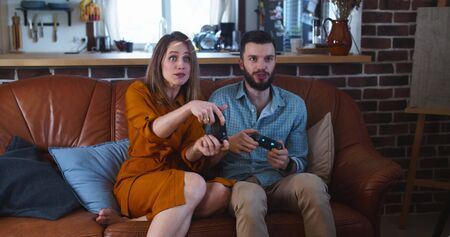 Cheerful happy young Caucasian couple play videogame against each other having fun at home, man is winning slow motion.