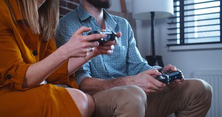 Close-up young Caucasian man and woman play videogame against each other, having big fun together at home slow motion.