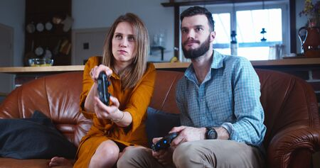 Young happy Caucasian married couple play console videogame with joysticks having big fun together at home slow motion.