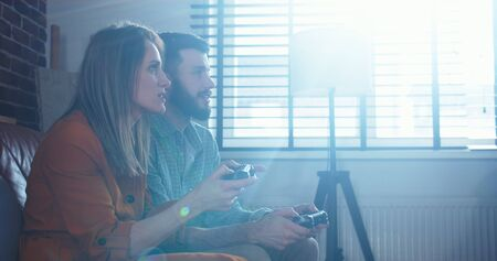 Lens flare shot of happy young Caucasian couple playing videogames against each other having fun at home slow motion.