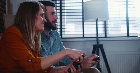 Side view young happy European couple of friends play console videogame with joysticks having fun at home slow motion.