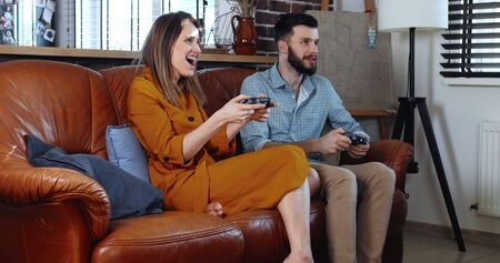 Cheerful young Caucasian man and woman play console videogame with joysticks enjoying fun together at home slow motion.