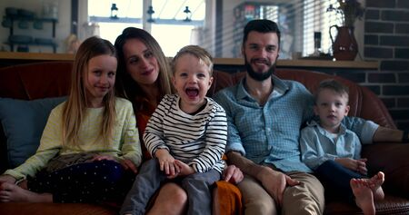 Family portrait, happy young Caucasian parents and three cute children look at camera at home on the couch slow motion