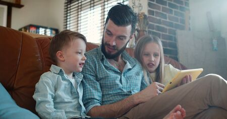 Cute little Caucasian son and daughter read and play together with father using tablet at home on couch slow motion.