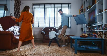 Family fun concept. Happy young European father and mother fight pillows with cute little son in modern home slow motion