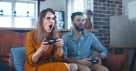 Happy young cheerful Caucasian man and woman play videogames at home enjoying fun leisure vacation time slow motion.