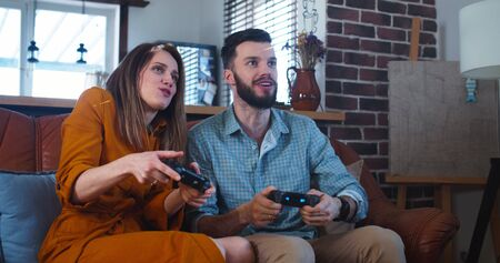 Young cheerful Caucasian husband and wife play videogames against each other at home enjoying leisure time slow motion. Foto de archivo